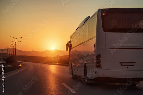 White bus driving on road towards the setting sun Poster