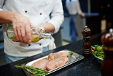 Chef pouring olive oil on raw chicken steak - 138691921