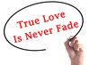 Hand writing True Love Is Never Fade on transparent board