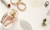 светлый фон с женскими духами в стеклянном красивом флаконе и украшениями  - 138716396