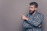 Fototapety Handsome smiling bearded man showing direction with finger