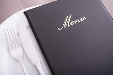 Closeup on menu, arranged table with cutlery and dishes