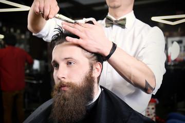 Barber making modern male hairstyle