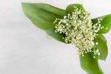 spring flowers lily of valley on white wooden table, top view