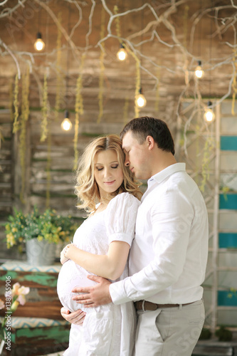 Poster happy husband and pregnant wife in a cafe tenderly hugging and holding belly