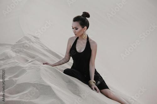 Fashion asian woman model posing in luxury dress in desert Poster