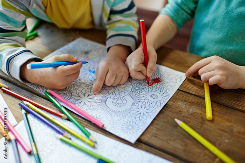 Foto Murales Close-up shot of two pairs of little hands coloring mandala with felt-tip pens, pencils of different colors and illustrations laid on wooden table