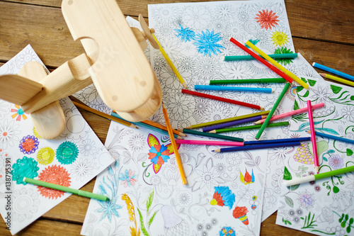 Pencils, felt-tip pens, pages from coloring books, toy plane located on wooden t