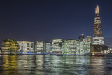 Cityscape of London at night with office building and colorful Thames.
