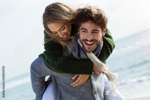 Happy young couple enjoying the day in a cold winter on the beach. - 138835578