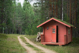 Red wooden hunting lodge with grass on the roof near the road in the forest