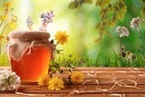 Honey pot with green nature background with flowers