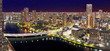 Night Tokyo panorama with wide angle aerial view of Sumida river in illuminated Tokyo with bright bridges, skyscrapers and dark cloudy sky