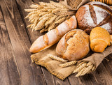 assortment of baked bread on wood table - 138874928