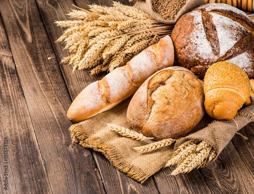 Fototapeta assortment of baked bread on wood table