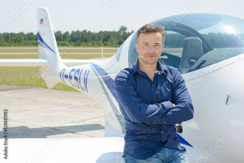 Portrait of man sitting on wing of aircraft