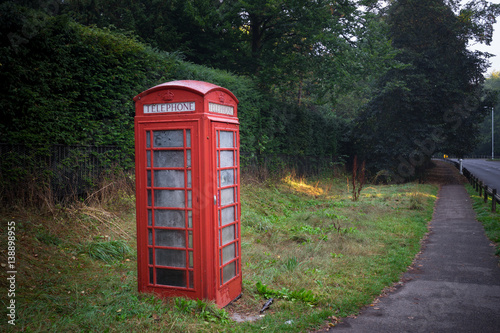 Red telephone booth beside the empty road in Cambridge, England Poster
