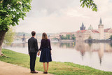 young couple holding hands and watching the Prague cityscape from the riverside