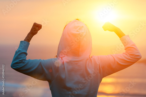 Fototapeta Back view of strong motivated woman celebrating workout goals towards the sun. Morning healthy training success.