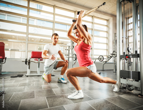 Poster Young female with sport body doing workout with her instructor at the gym.She working on her triceps and man push her to the limits.