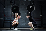 Motivational wide shot of young man and woman holding huge heavy barbells overhead looking at each other - 138958966