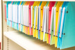 set of multi colored folders / files in metal enclosure / closet
