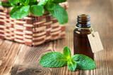 Peppermint essential oil in a glass bottle with a tag on wooden background - 138974364