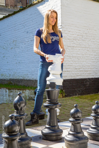 Young girl playing outside chess Poster
