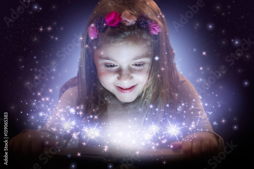 Beautiful little girl reading magic book; fantasy concept Poster