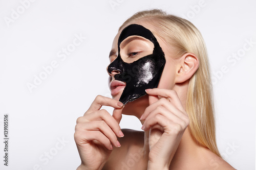 A young girl takes a black mask from her face.