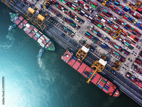 Leinwandbild Motiv container ship in import export and business logistic.By crane ,Trade Port , Shipping.cargo to harbor.Aerial view.Water transport.International.Shell Marine.Top view.
