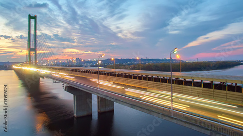 Foto op Canvas Automobile and railroad bridge in Kiev, the capital of Ukraine. Bridge at sunset across the Dnieper River. Kiev bridge against the backdrop of a beautiful sunset in Kiev. Bridge in evening sunshine
