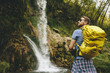 Young hiker stopped beside a mountain waterfall to rest