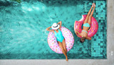 People relaxing on inflatable ring in pool - 139129315