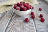 Замороженные вишни лежат в тарелке. Тарелка находится на деревянном столе .  Натуральные продукты природы. Вишни покрыты инеем.
