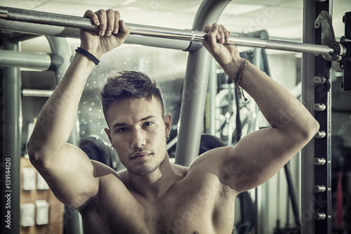 Muscular, shirtless young man resting in gym during workout, showing muscular torso, pecs