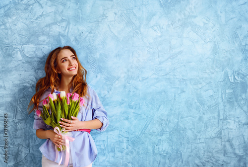 young girl with bouquet of flowers on the blue wall background