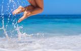 woman legs, jumping on the beach