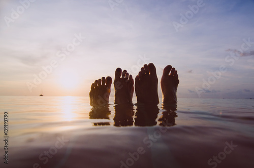 legs in the sea at sunset