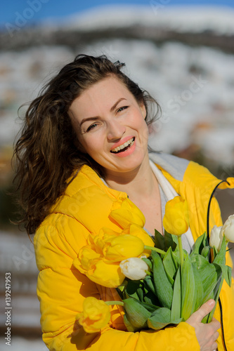 Poster Charming woman with a bouquet against the background of mountain tops