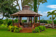 A gazebo in a  lush green garden in Maui, with a blue sky background
