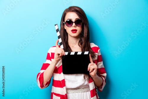 beautiful young woman with cinema clapper standing in front of wonderful blue background