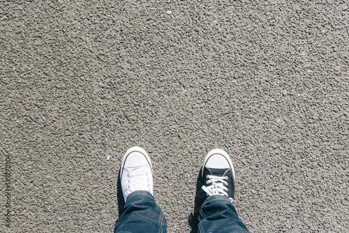 Black and white shoes on asphalt, high angle