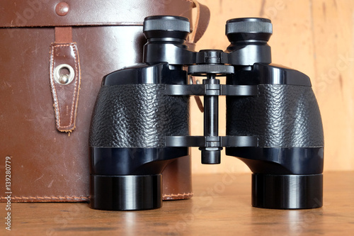 Vintage Porro prism black color binoculars and closed brown hard leather case on wooden background front view closeup
