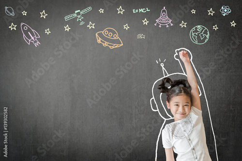 Happy little asian girl kid in astronaut suit doodle drawing, universe space out of earth planet on school black class chalkboard chalk board background Creative innovation educational conceptual idea