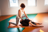 yoga instructor assisting student in exercise