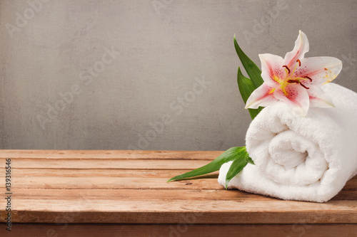 Foto op Plexiglas Spa Spa and wellness concept with white towel and flower on wooden table over rustic background