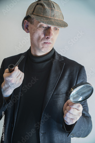 sherlock holmes in studio detective at work with magnifying glass and pipe Poster