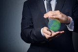 businessman in a suit holding planet earth. Planet earth in the hands. Protect the planet earth.