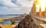 Greece. Rhodes. Acropolis of Lindos. Doric columns of the ancient Temple of Athena Lindia setting sun above the columns